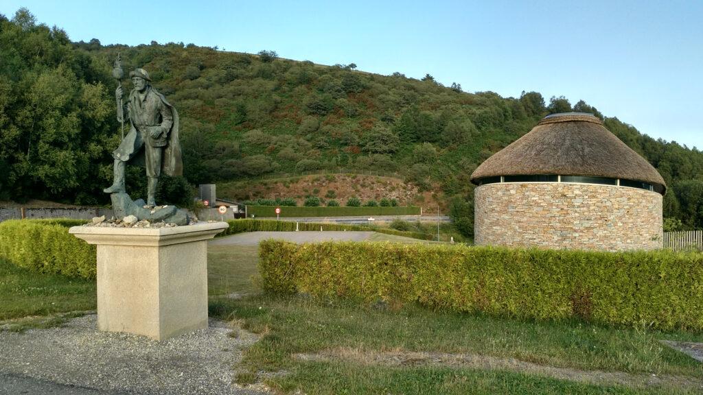 Estatua de Hermann Künig y palloza a la entrada de Pedrafita