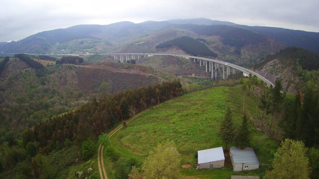 Perspectiva aérea del Camino de tierra en primer término bordeando la sierra de Horta y el viaducto de la A6 al fondo